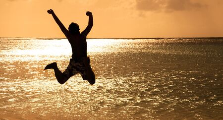 high life: Happy Young man jumping on the beach at sunset