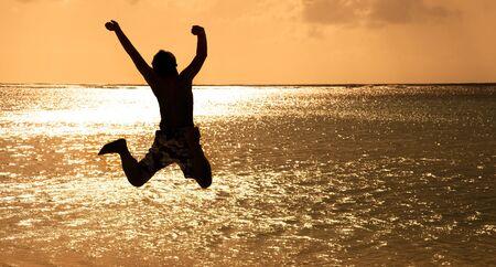 ni�o saltando: Joven feliz saltando en la playa al atardecer