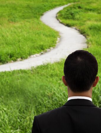 grass  plan: Business man thinking and watching the curved road Stock Photo