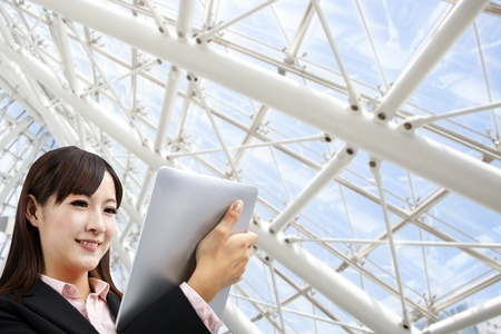 chinese business: Business woman holding tablet pc in the modern office
