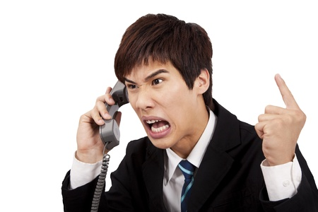 complain: angry businessman screaming on the phone and isolated on white background