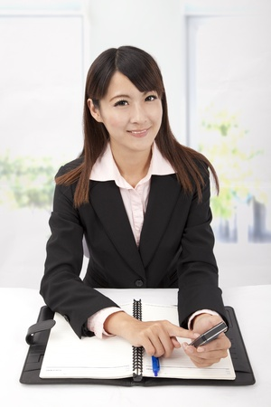 Portrait of a smiling young business woman holding touch phone in the office photo