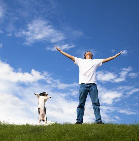dog health: giovane uomo rilassarvi sul campo verde con il suo cane