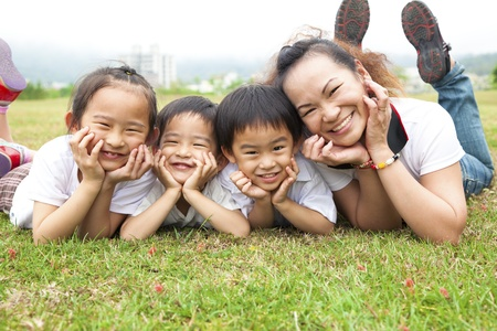 Happy mothers day. asian mother and her children on the green field photo