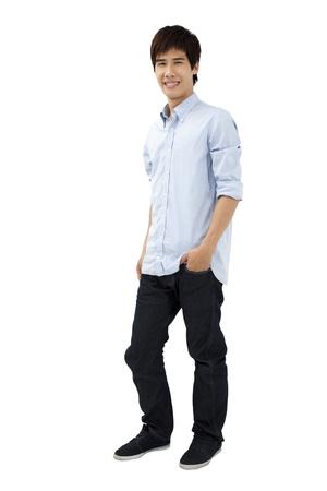 var�n: joven hombre de pie con las manos en los bolsillos
