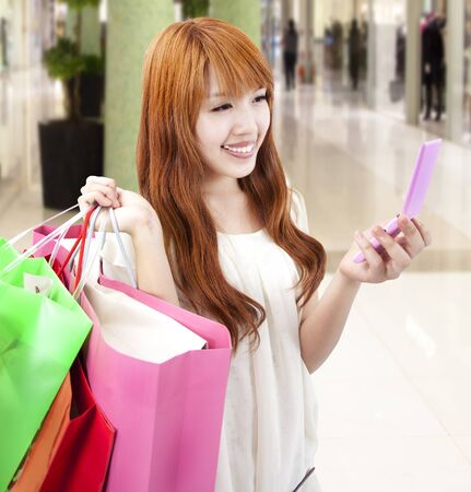 young woman holding mobile phone and shopping bag in the mall photo