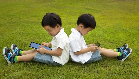 Two kids using touchscreen tablet PC on the grass  photo