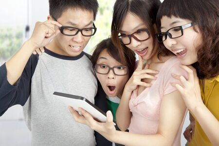young group using tablet pc and surprised photo