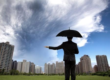 klima: Geschäftsmann im dunklen Suiten mit Sonnenschirmen und beobachten Sturm