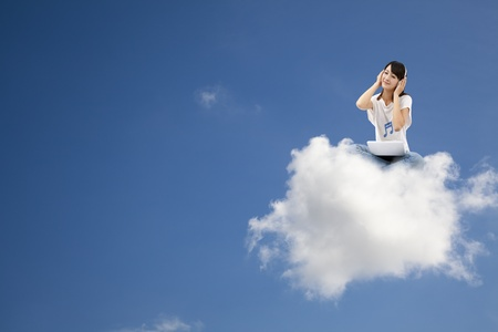 smiling woman listen to music and sitting on the cloud with computer photo