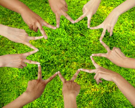 Many different hands connecting to star shape with grass background photo