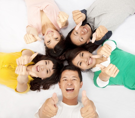 group of asian young people lying together with thumb up photo