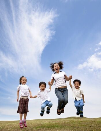 leaping: happy asian family  jumping on the grass field. mother and her children