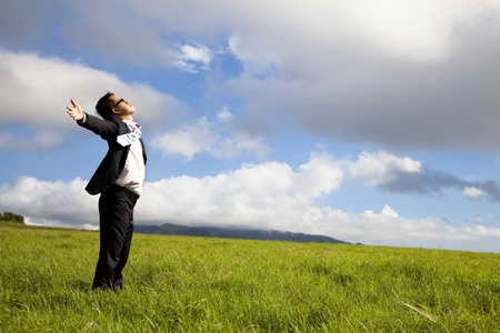 young man in green  field under blue skies photo