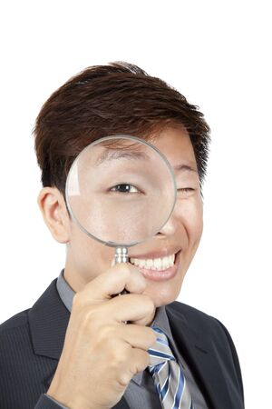 asian businessman holding magnifier over his eye photo