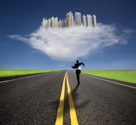 vision futuro: hombre de negocios que se ejecuta a la futura ciudad con su sombra