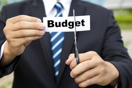 schneiden: Gesch�ftsmann mit einer Schere schneiden Etikett Budget Lizenzfreie Bilder