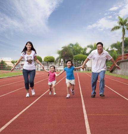 familia feliz asiático correr juntos en la pista del Estadio