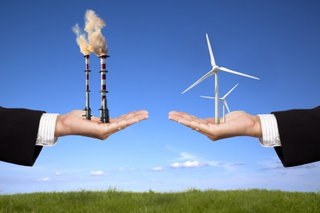 global warming: pollution and clean energy concept. businessman holding windmills and refinery with air pollution Stock Photo