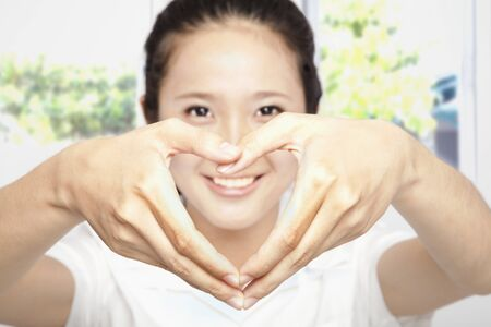 smiling young woman make heart shape Stock Photo - 10118404