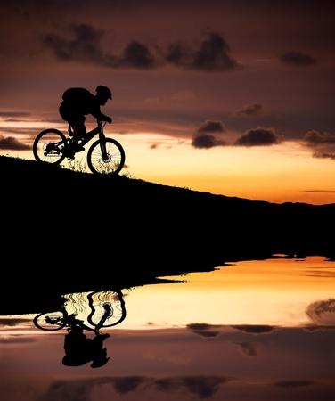 mountain bicycle: Silhouette del motociclista della montagna con la riflessione e il tramonto