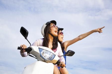 vespa: las ni�as felices montando scooter disfrutan de vacaciones de verano Foto de archivo