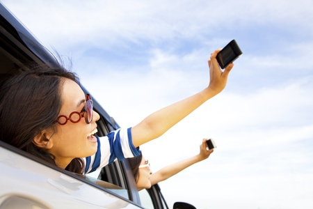 happy young woman  holding camera and mobile phone taking photos in the car