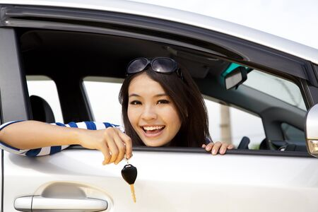 auto leasing: young happy woman in car showing the keys Stock Photo