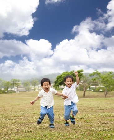 is playful: felices niños asiáticos que se ejecutan en la hierba Foto de archivo