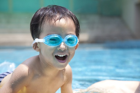 happy asian kid in swimming pool photo