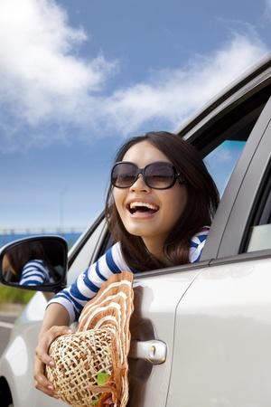 conducci�n: mujer feliz sentada en el coche y mirando hacia atr�s