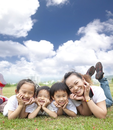 kid friendly: happy asian family on the grass with cloud background