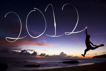 happy new year 2012. young man jumping and drawing 2012 by flashlight in the air on the beach before sunrise Stock Photo - 10445447