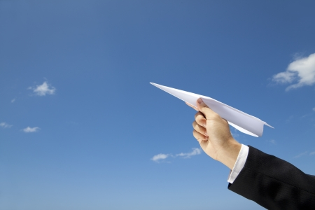 airplanes: hand of Businessman letting an airplane made of paper fly over blue sky