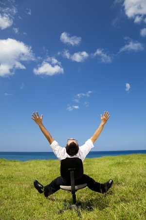 feel: relaxed businessman sitting on the chair in green field Stock Photo