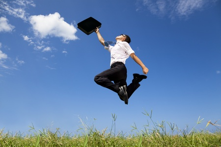 motivating: happy and successful businessman jumping on the field Stock Photo