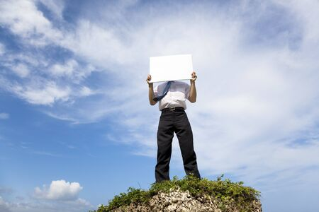 Businessman standing on a peak and holding blank billboard photo