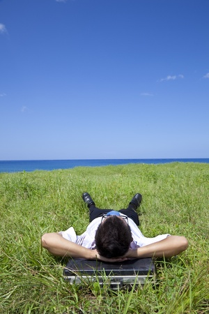 Businessman lying on green grass and watching the blue sky photo