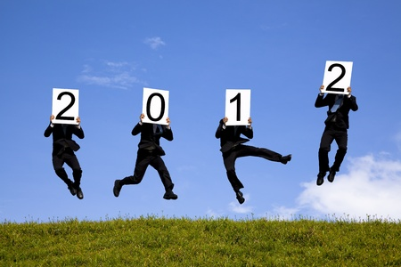 amaze: businessman holding 2012 billboard and jumping on the green field Stock Photo