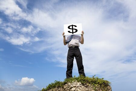 Businessman standing on a peak and holding money mark photo