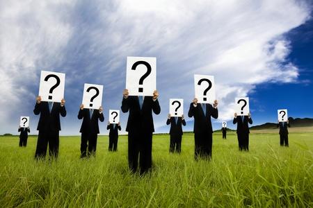 signo de interrogacion: grupo de negocios en traje negro y el símbolo de la celebración de un signo de interrogación