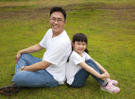 happy father with daughter sitting on the grass photo