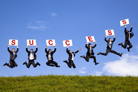 success business: happy businessman holding success text  and jumping on the green field