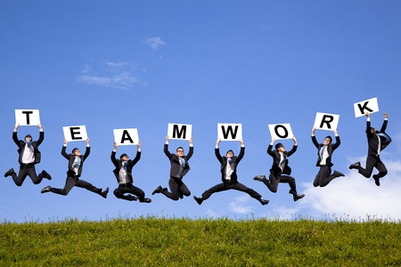 jumping businessman: happy businessman holding teamwork text and jumping on the green field