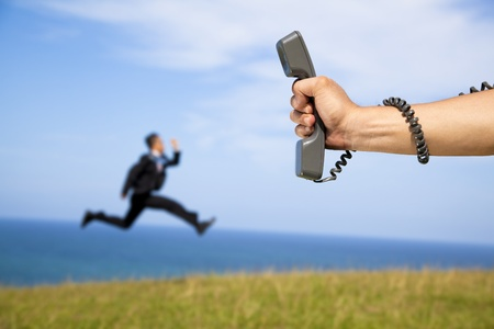 hand holding phone and running businessman