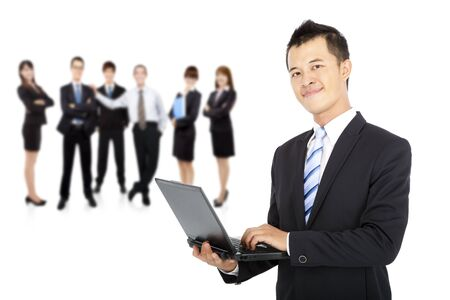computer support: smiling businessman holding laptop and successful business team Stock Photo