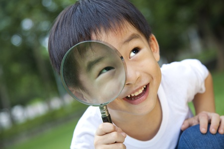 magnify: asian boy holding magnifier Stock Photo