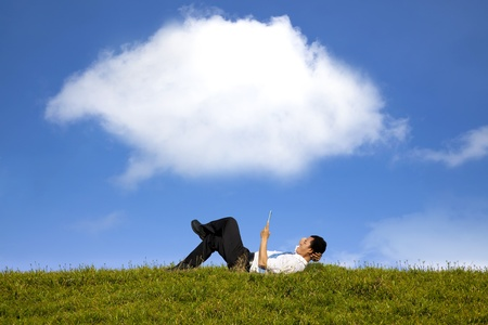 green computing: cloud background and happy businessman working with tablet pc on the green grass