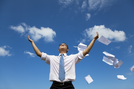 relaxed businessman throwing away papers  to the sky photo