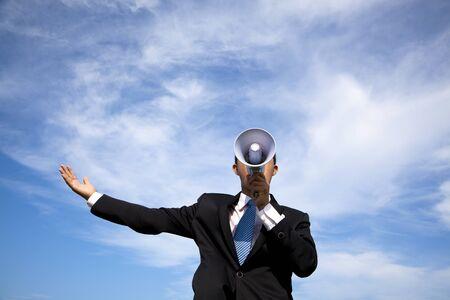 megafono: Hombre de negocios la celebraci�n de meg�fono y nubes de fondo Foto de archivo